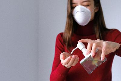 Woman apply hand sanitizer with a face mask on