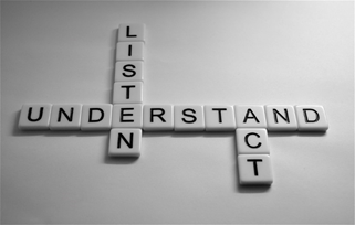 Scrabble pieces on a white background spelling out Listen, Understand and Act.