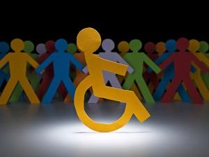 Paper cut outs of a person in a wheelchair with other people in the background.