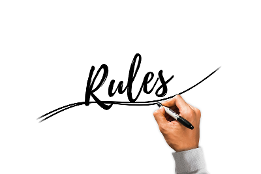 Hand written in black pen on a white board the word rules