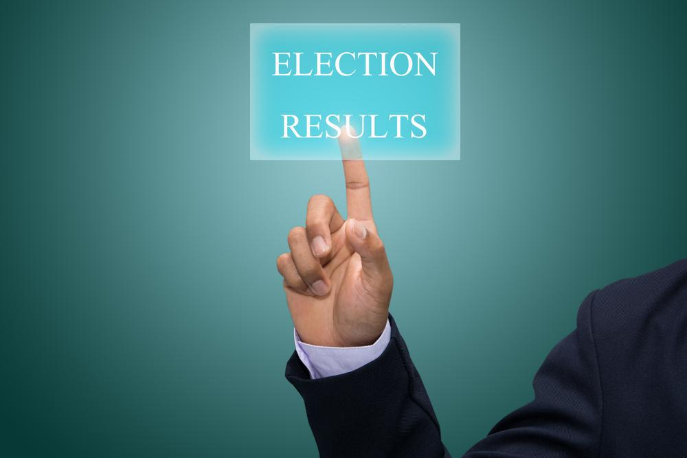 A persons finger pressing a Election results button on a blue screen